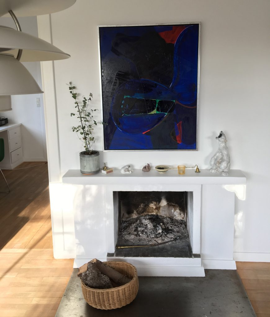 Oliemaleri af Nes Lerpa ophængt på væg med direkte sollys der skaber genskin og liv i værket.